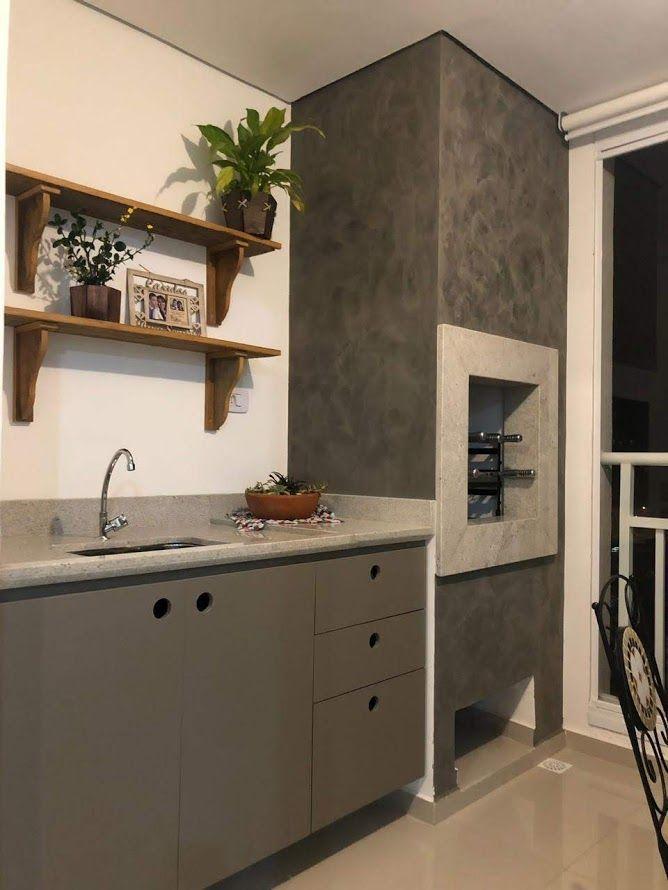 Área gourmet com churrasqueira revestida de cimento queimado, armários cinza, pia de mármore, prateleiras de madeira e piso porcelanato neutro.