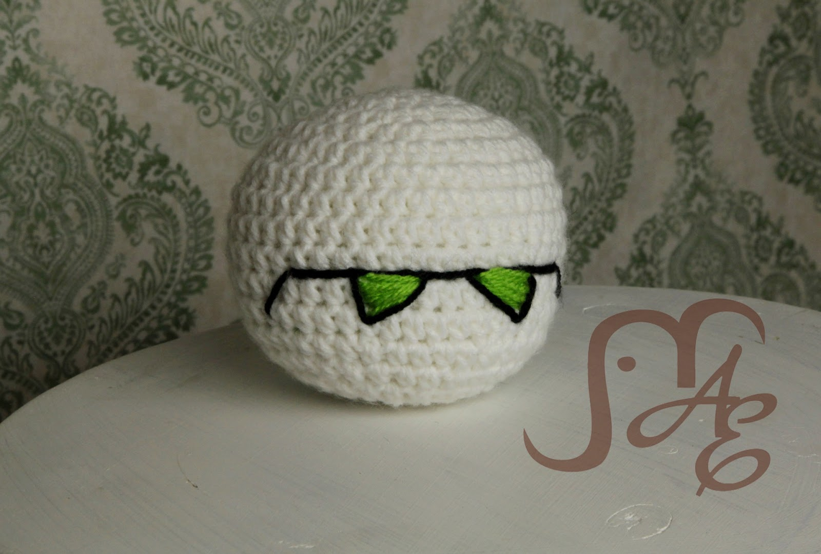 White crocheted ball with green triangles as eyes.