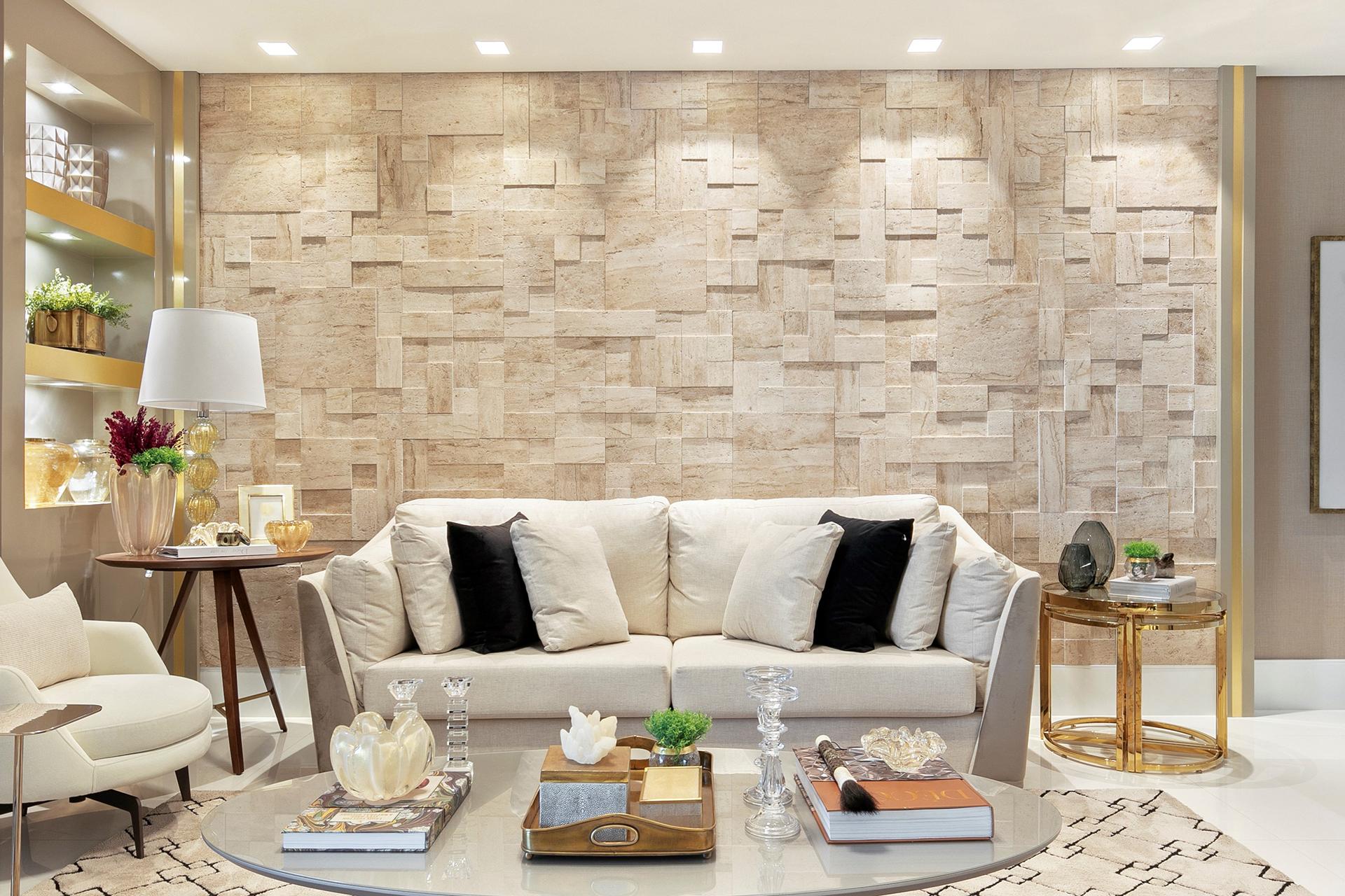 Sala com sofá branco e almofadas pretas e brancas, poltrona branca, mesinha de centro oval cinza, mesinhas de canto dourada e marrom e parede de fundo com revestimento 3D bege Mosaico Estrusco Travertino