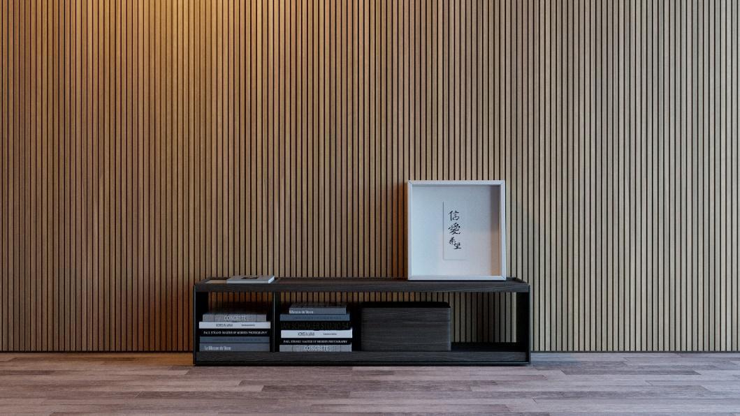 ambiente com parede revestida de madeira ripada, piso de madeira e móvel pequeno com livros e quadro.