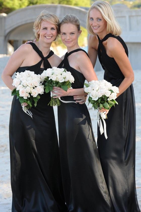 A group of women in black dresses holding white flowers  Description automatically generated with medium confidence