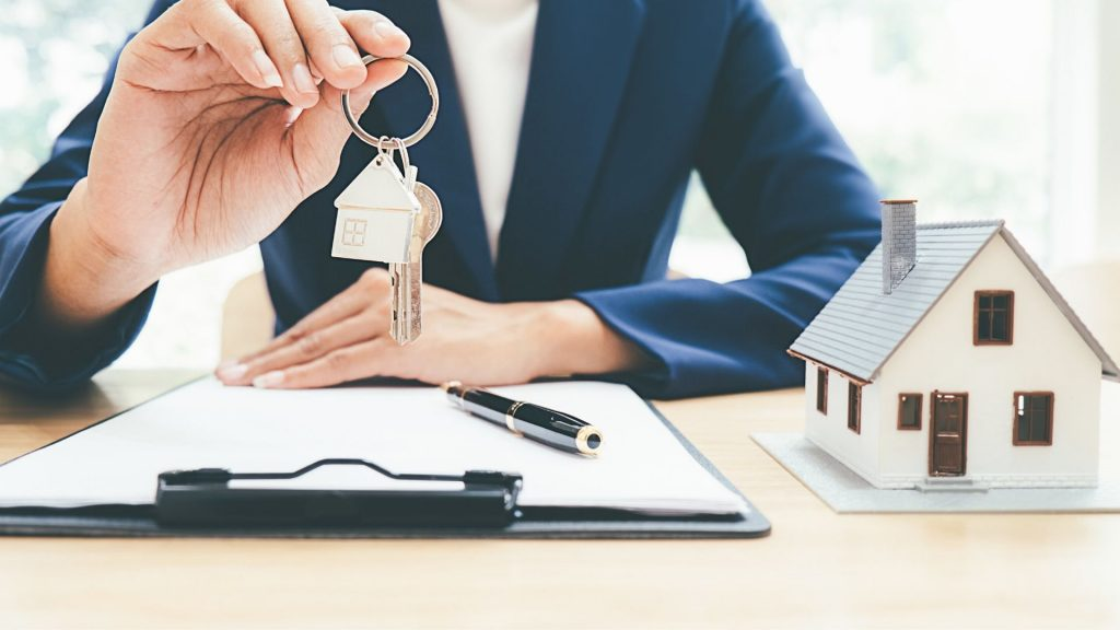 Orang agen properti yang sedang memegang kunci rumah