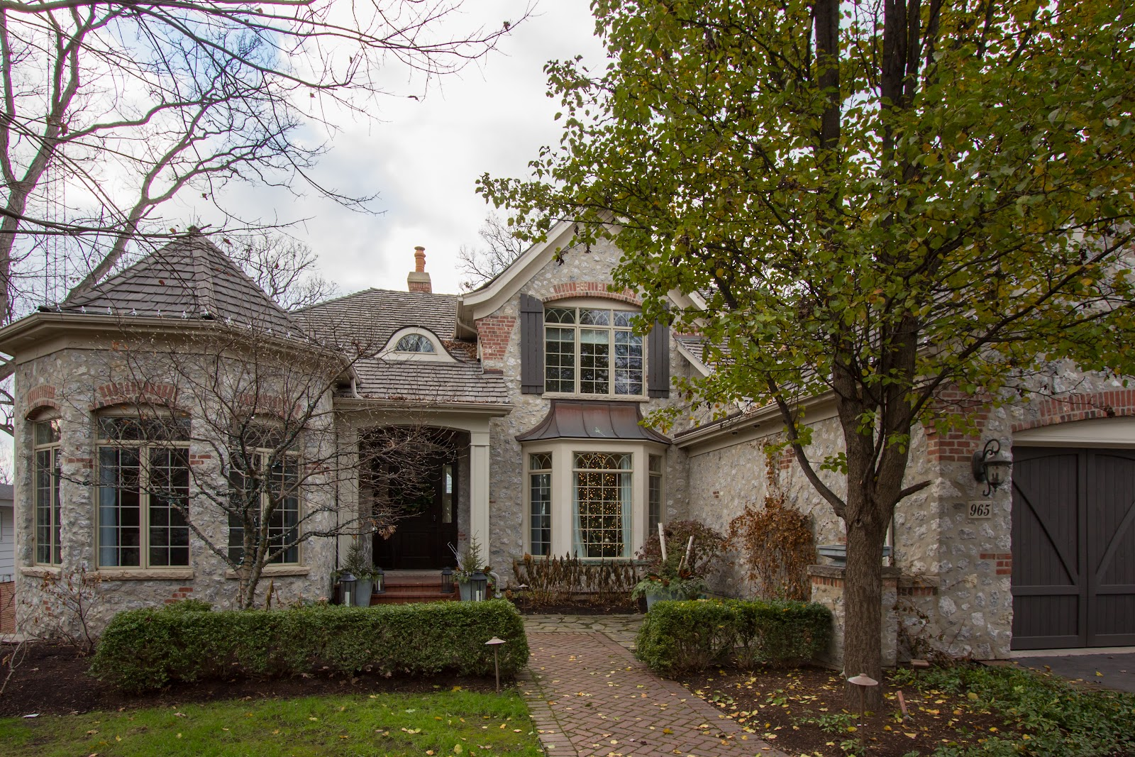 French Provincial Style Home in the autumn with entryway path and hedge