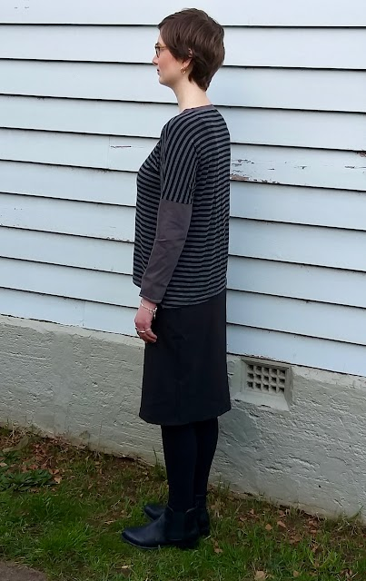 Siobhan stands in front of a weatherboard house. She wears a drop shoulder knit tee with grey/black striped body and concrete grey neckband and sleeves, with black straight knee length skirt, black leggings and ankle boots. She is side on to the camera to showcase the well-matched shoulder seam stripes.