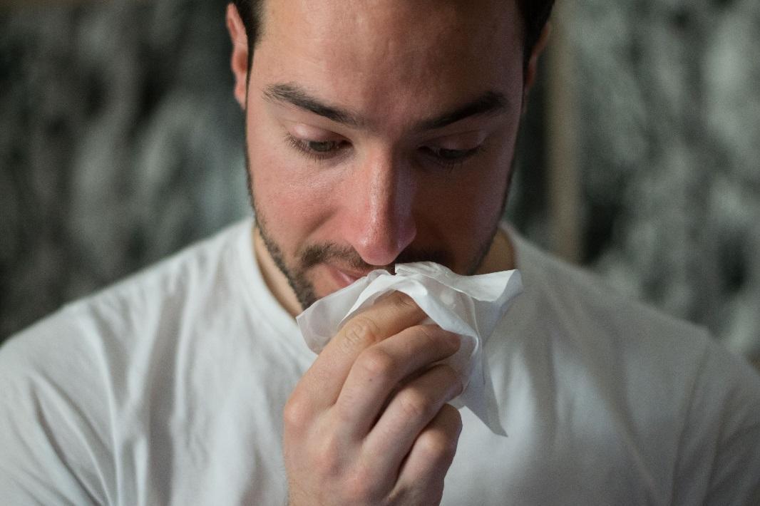 Persona con tos y un pañuelo