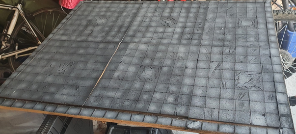 Board completely covered with cork tiles etched to be dungeon tiles and painted grey.