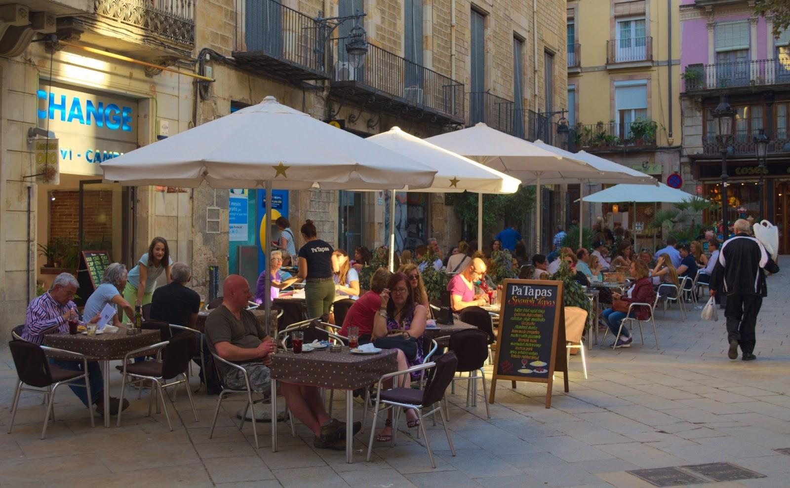 People eating and drinking on a bustling outdoor terrace in Barcelona.
