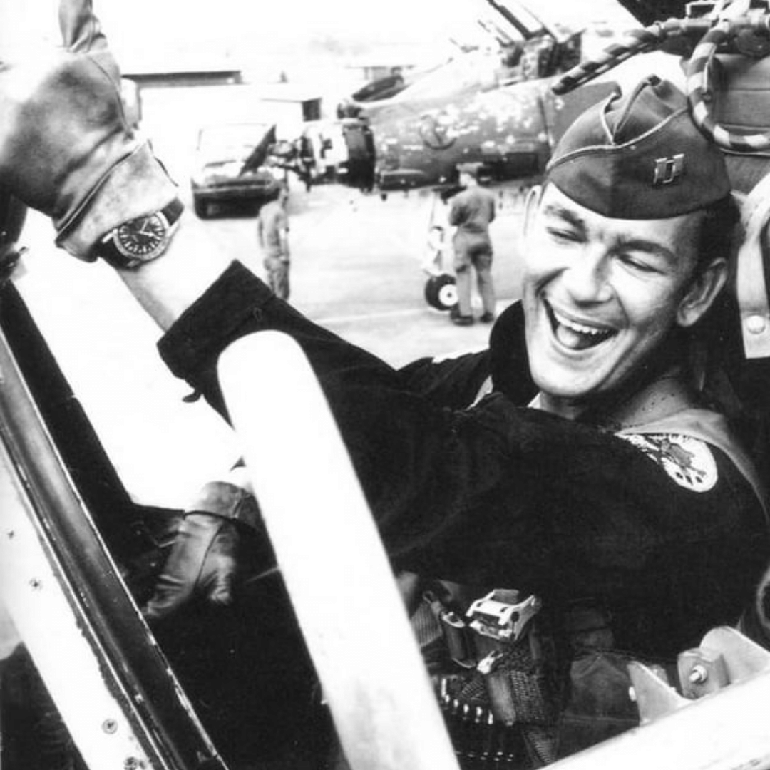 An old black and white photograph of a pilot wearing a Glycine Airman watch inside the cockpit of a fighter plane.