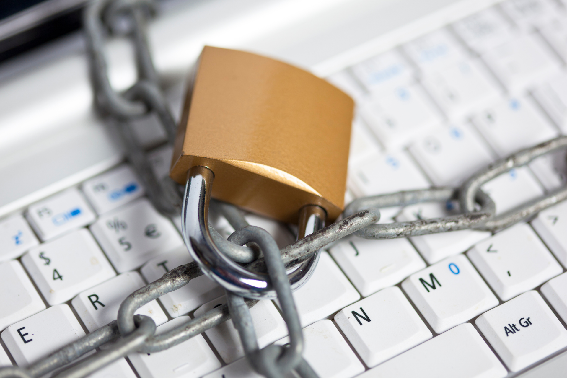 Alt text: A lock and chain on a computer keyboard.