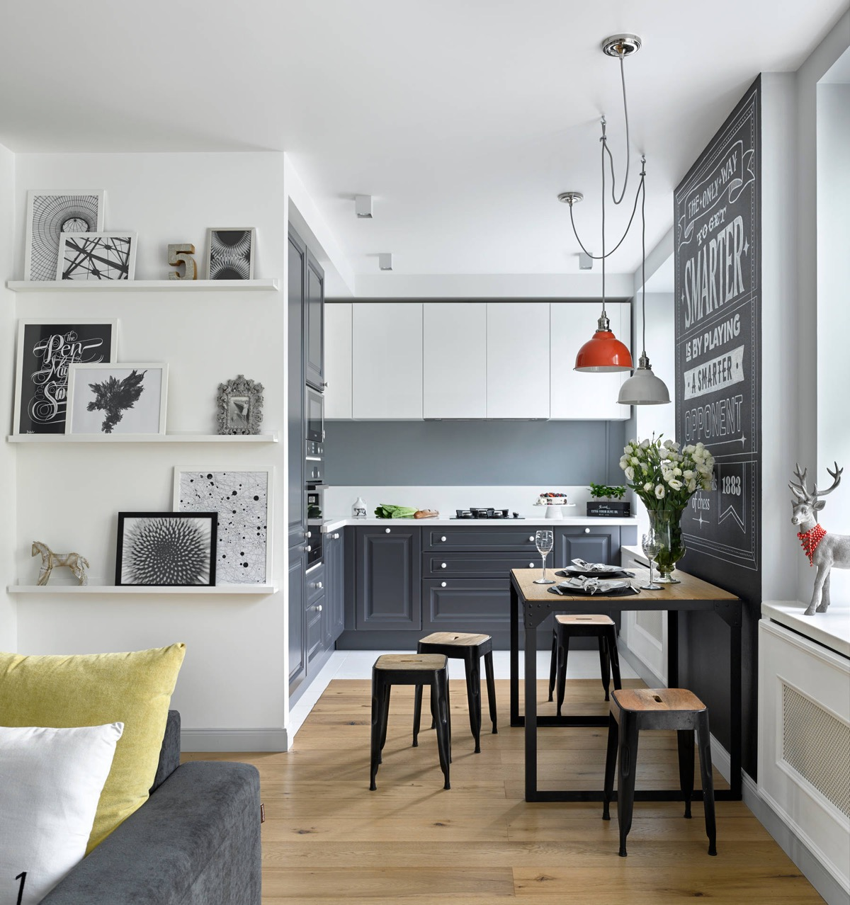 a small kitchen is positioned in the corner of the living room area. grey base cabinets and white upper cabinets give the small space some contrast. a wooden dining table separates the kitchen and living areas