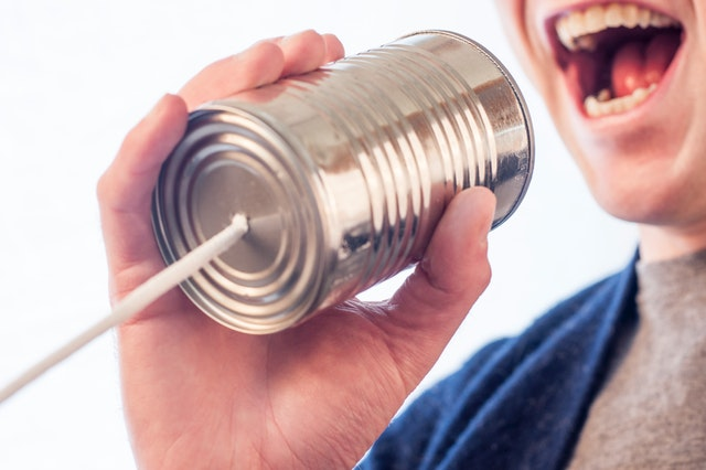 person using their voice to talk through a tin can with a string
