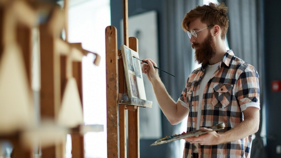 A man standing at an easel painting.