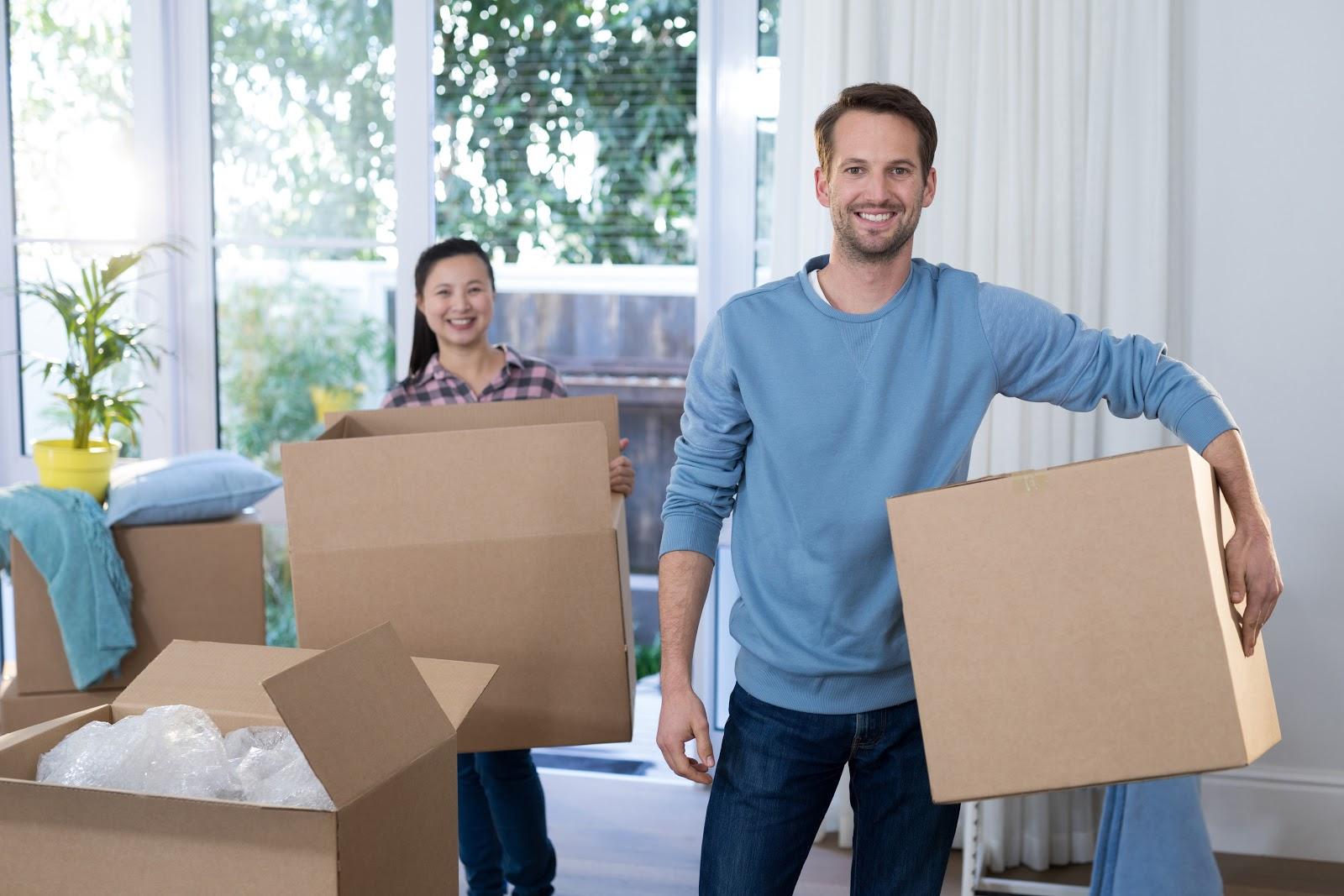 Um casal segurando caixas.
