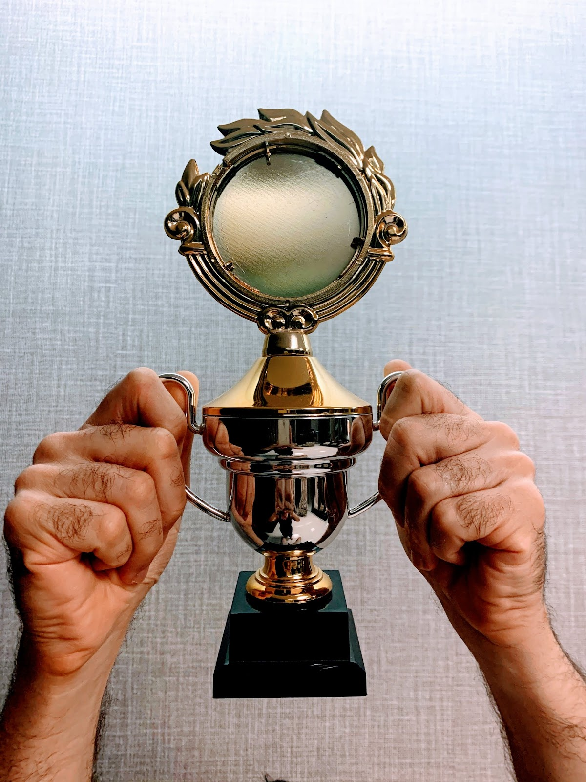 Two hands hold a shiny trophy. Your STEM Club participants will work harder with incentives like competition rewards.
