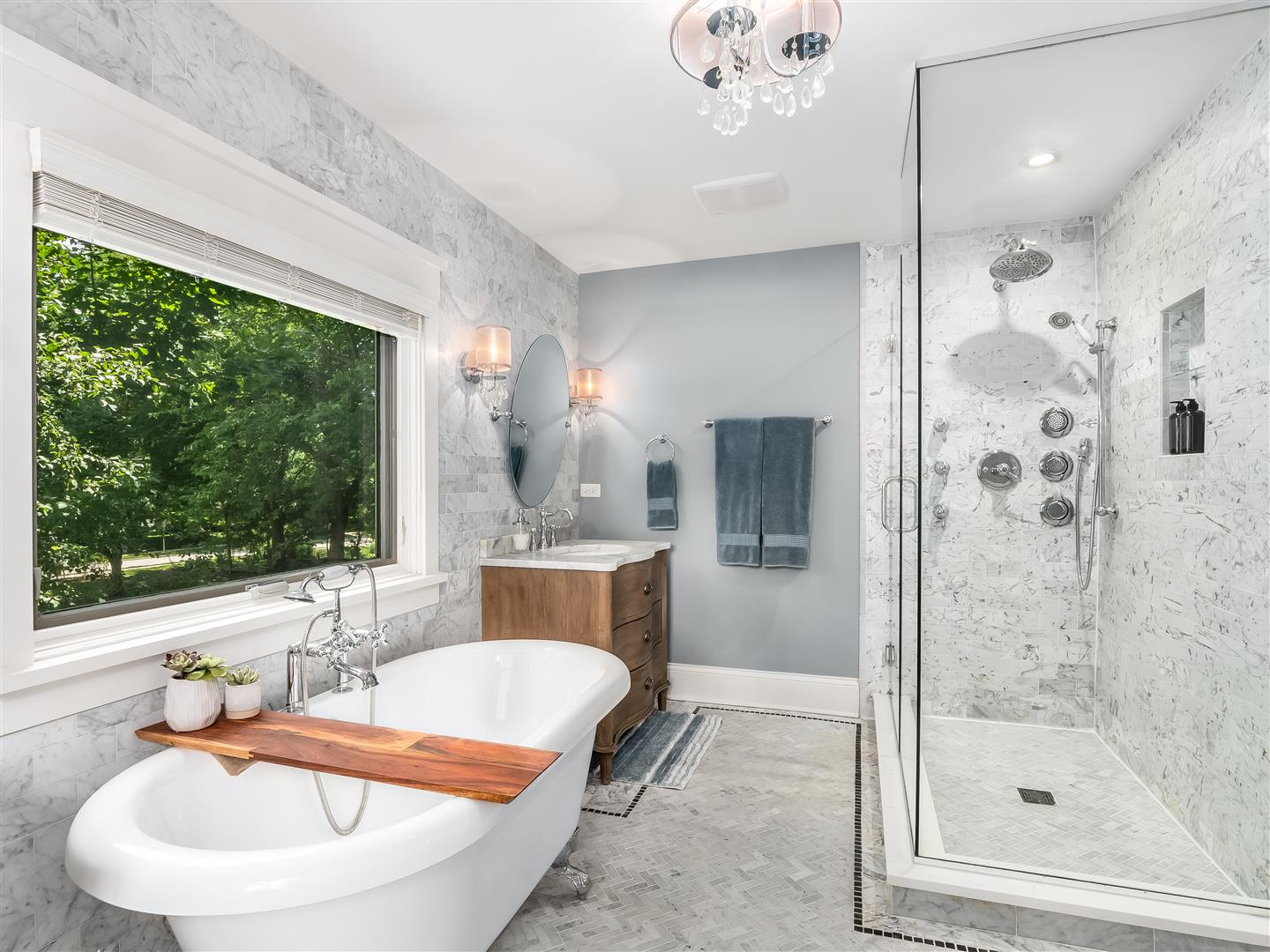 Luxury marble bath design with claw foot tub,  glass surround shower and natural wood elements