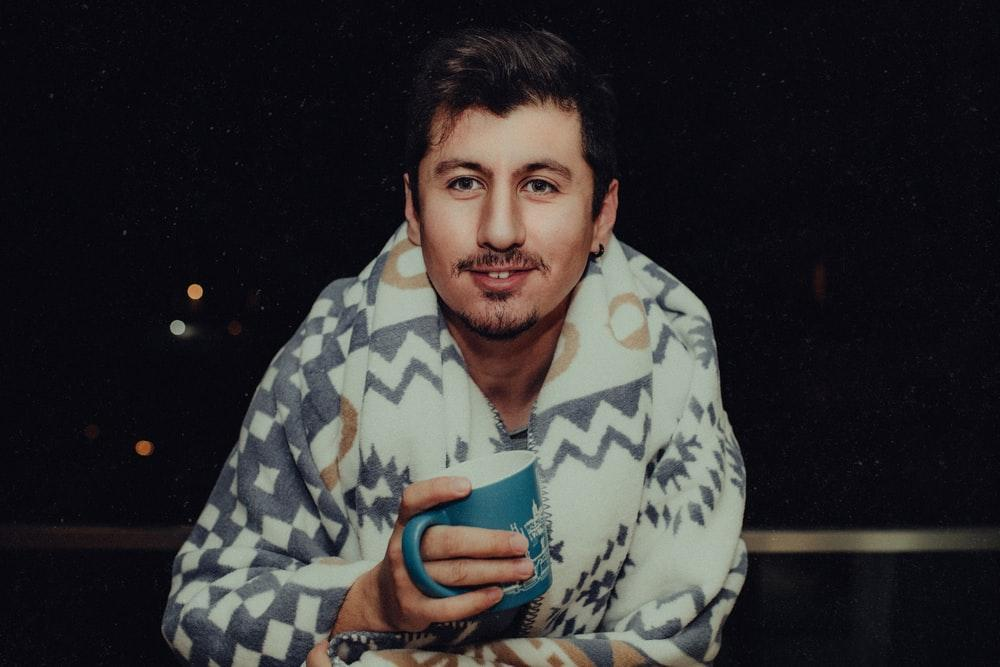 man in blue and white checkered dress shirt holding blue ceramic mug