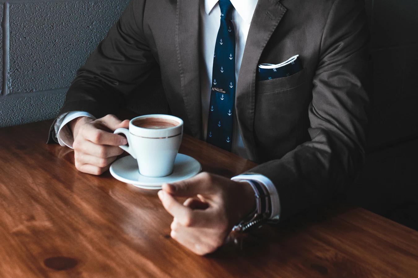 Osoba w formalnym garniturze pijąca kawę przy brązowym stole