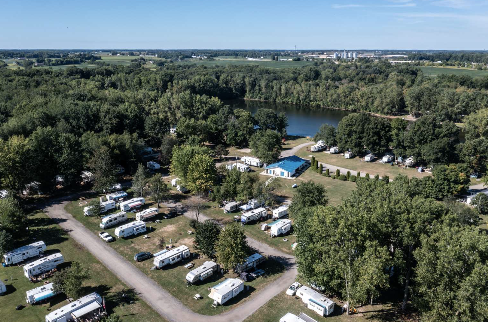 aerial view of campground with RVs parked and body of water