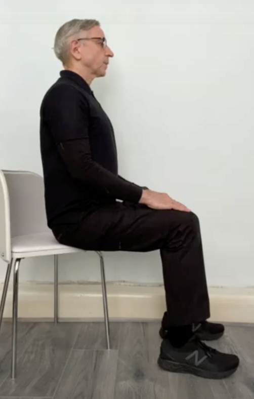 instructor sitting upright in chair with his back straight and hands resting on his lap