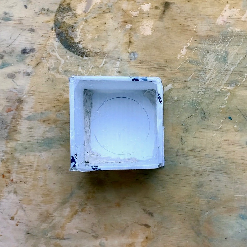 inside of corrugated box showing clay smushed into corners and edges