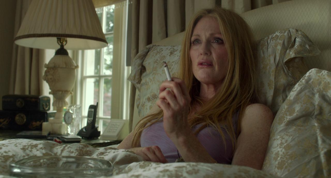 Julianne Moore as Havana in 'Maps to the Stars' (2014). Havana, a middle-aged woman with heavy makeup and plastic surgery, lies in a bed with ornate silk sheets. She is holding a cigarette and looking up with an apparent displeasure.
