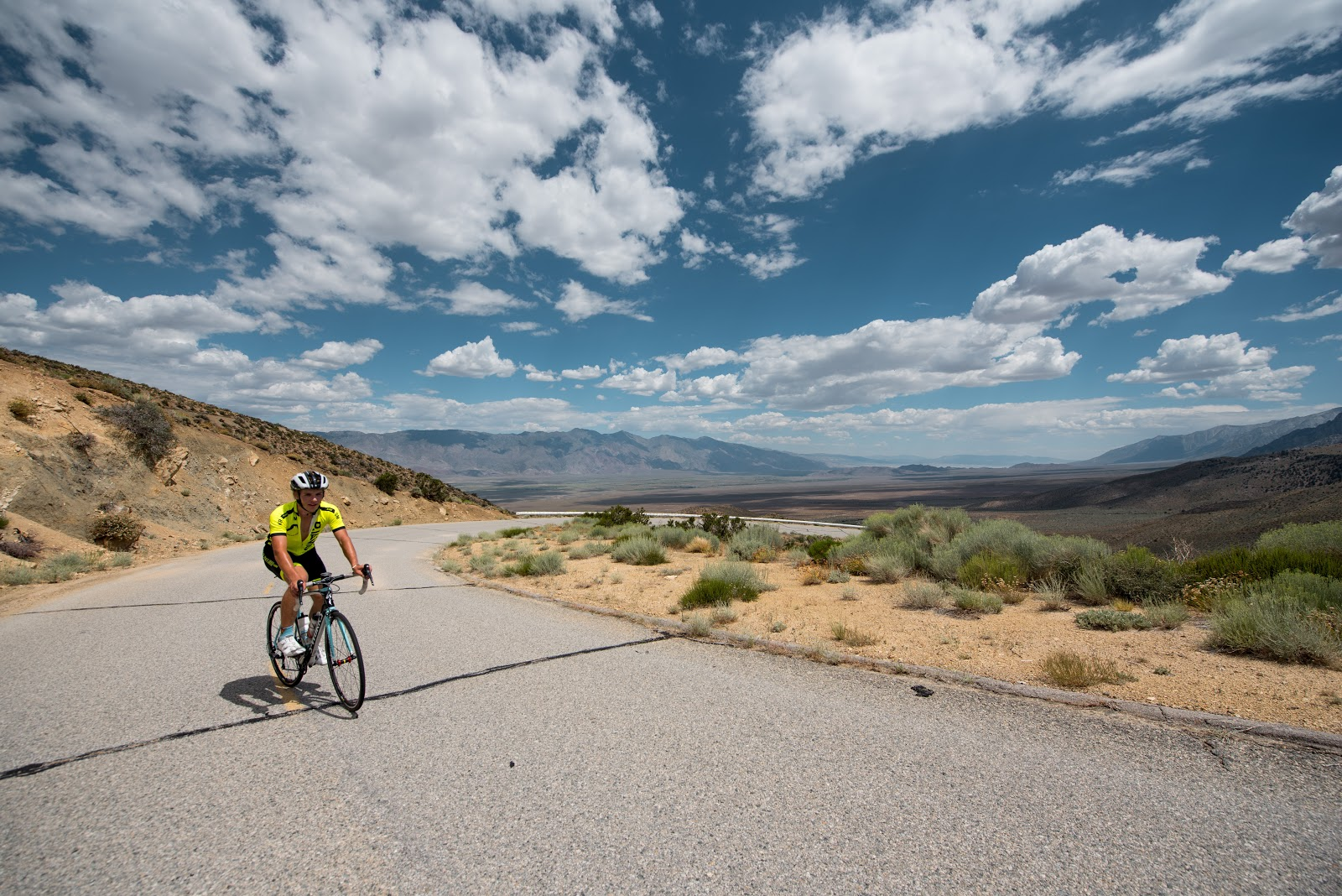 Bike climb  Owens Valley - pjamm cyclist on bike on road with clouds
