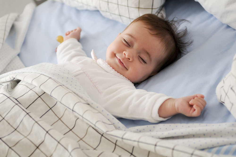Smiling baby lying on a bed while sleeping on blue sheets