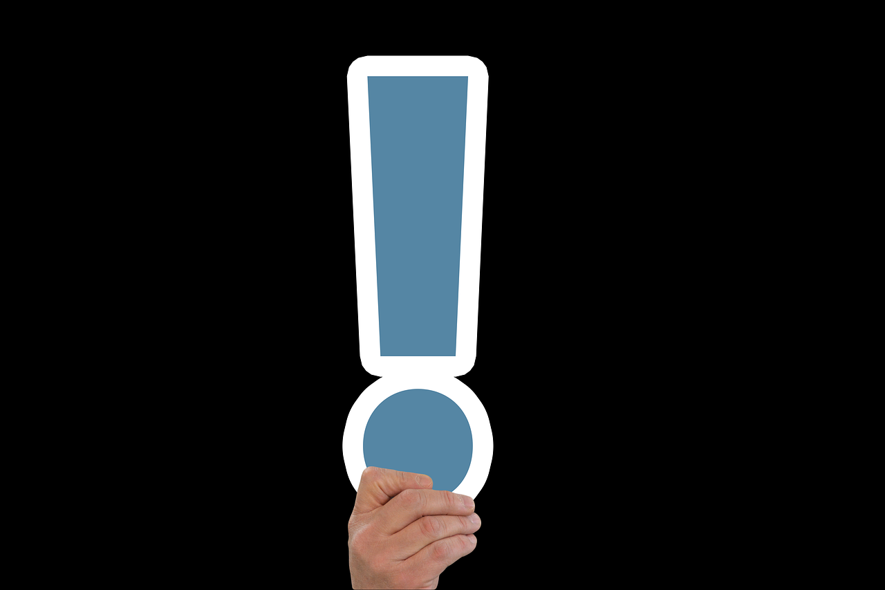 A hand holding a blue exclamation point