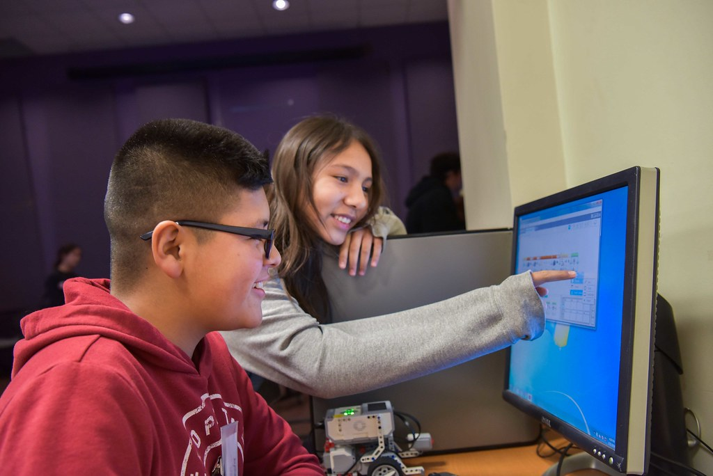 Two high school students share a smile as they discuss something on their computer screen. A young male student with glasses sits at the computer, while a female peer points to something on the screen as she is smiling.