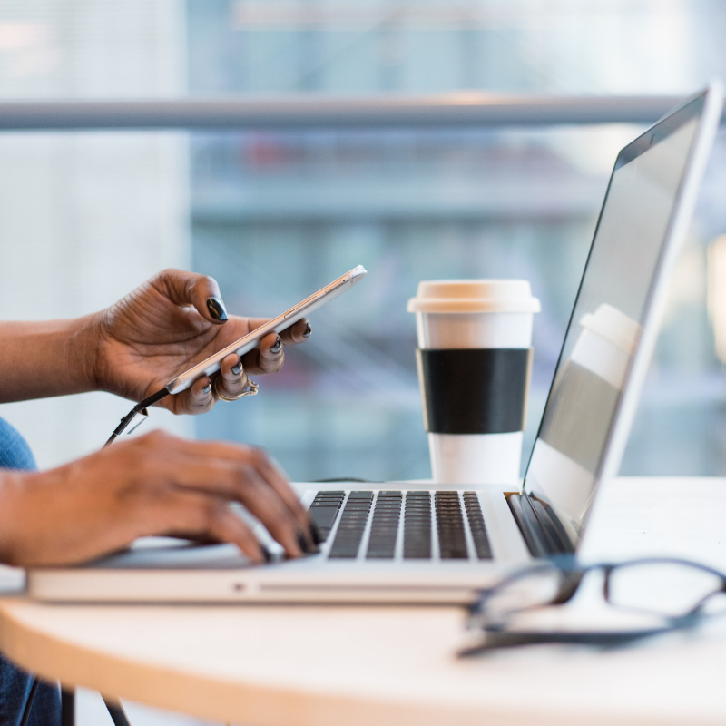 woman checking phone on laptop