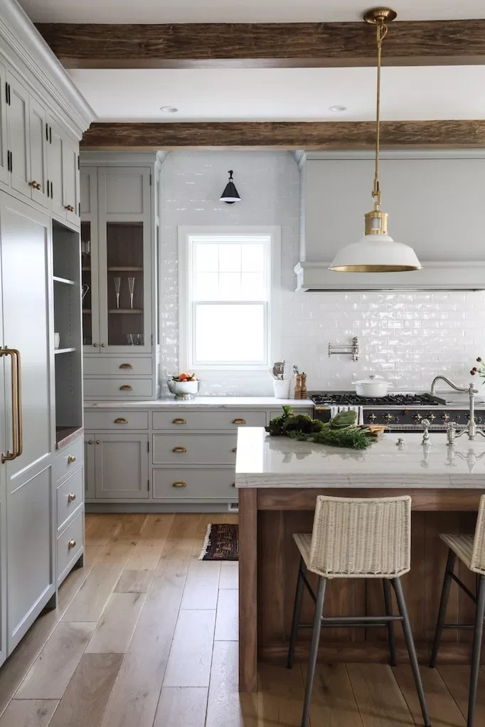 large bright modern farmhouse kitchen with light gray inset cabinets vintage hardware glossy white backsplash wood beams and oversized farmhouse kitchen island