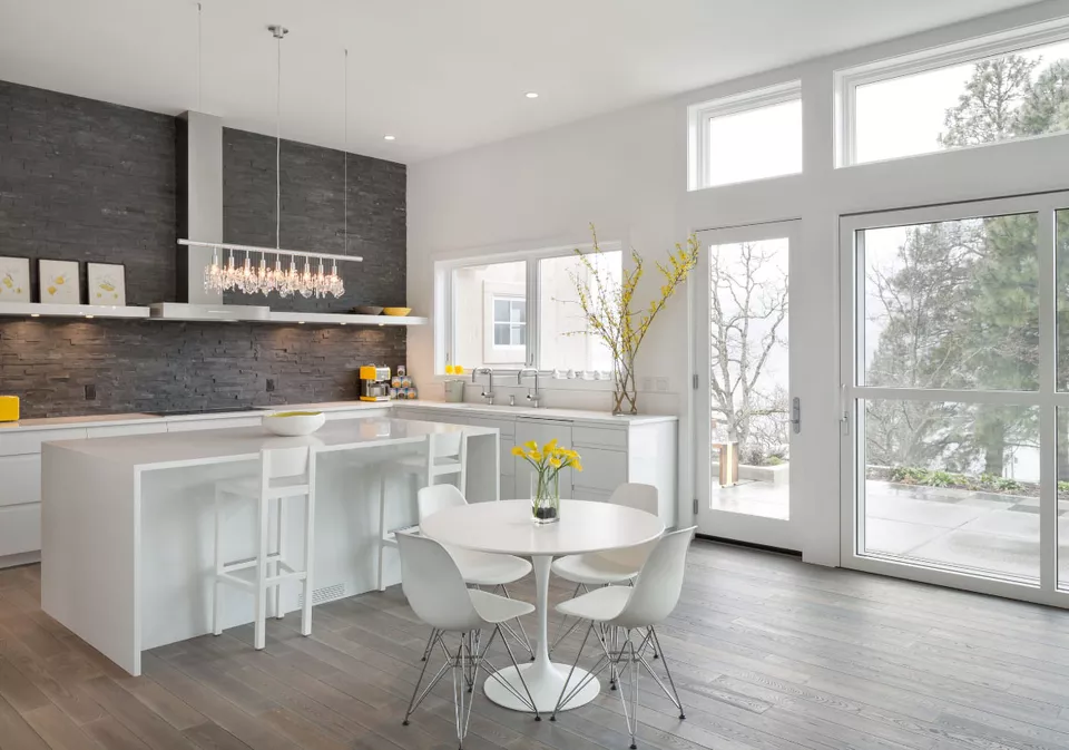 modern white kitchen with charcoal grey stacked stone backsplash, wooden floors, white waterfall marble island, open shelving, sliding doors and small modern dining area