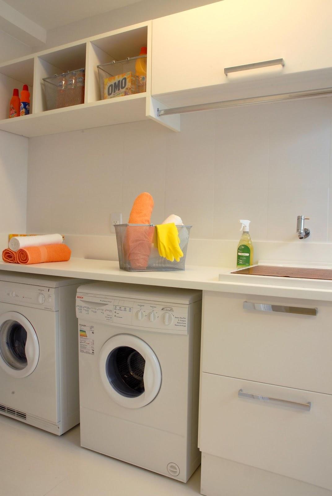 Imagem de uma área de serviços pequena e padrão, com duas máquinas de alvar e uma pia.