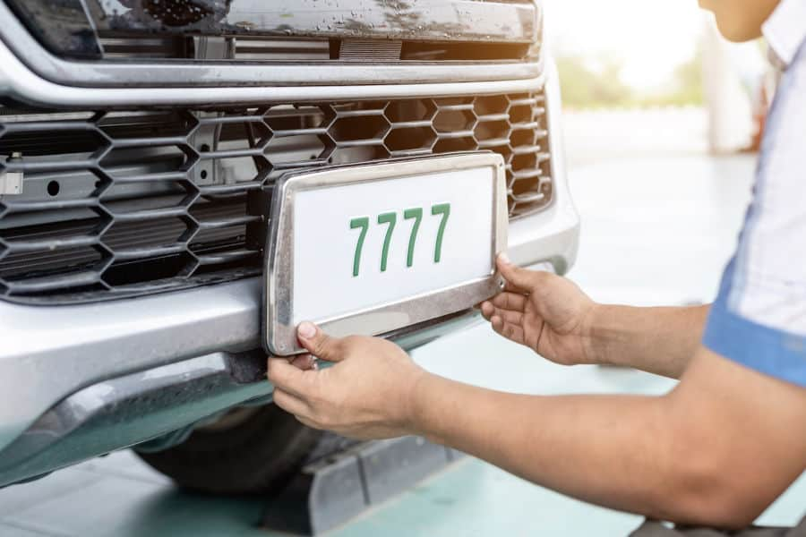 Man placing a new license plate on the front end of a vehicle