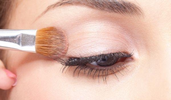 close up shot of brush applying eye primer on the eye