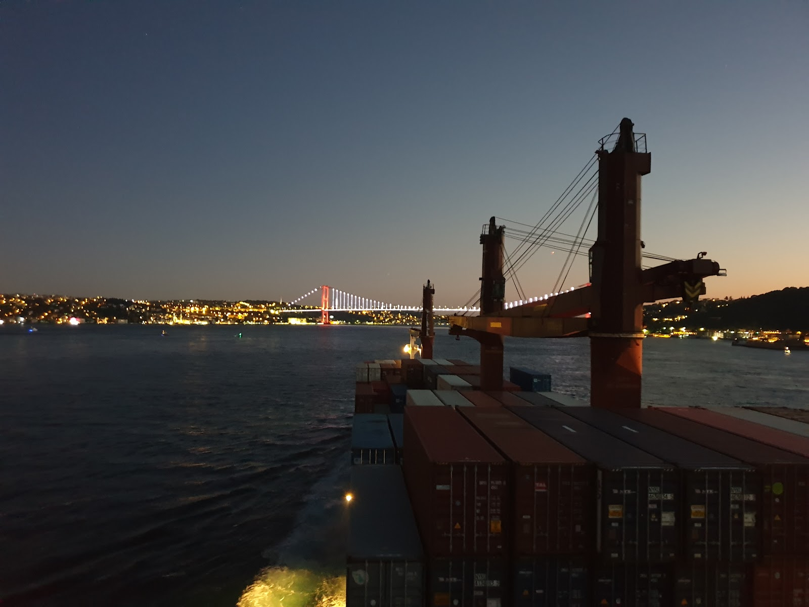 View from a container ship as it sails towards a bridge lit up by lights at night