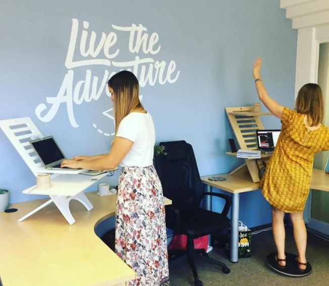 sit or standing desk option for work from home professional or coworker and employees, showing two women working in company office with live the adventure background wall
