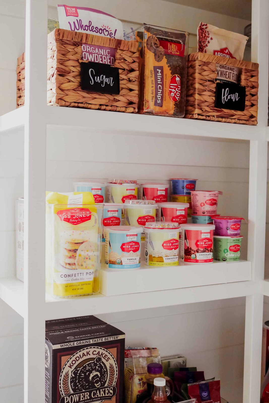 white pantry with shelving for food and extra organized shelving