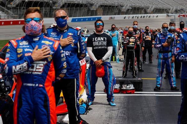 "Bubba Wallace, center, at the Atlanta Motor Speedway on Sunday, wants NASCAR to ban the Confederate battle flag at its races. ""Get them out of here,"" he told CNN. ""They have no place for them."""