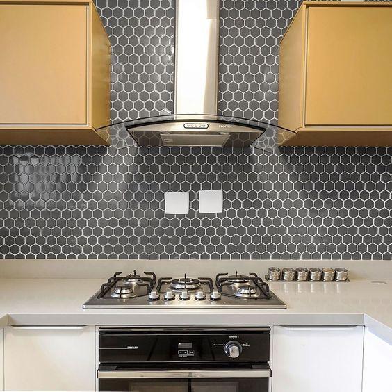 Cozinha com revestimento hexagonal azul em formato pequeno na parede da cozinha, bancada e inferior armário branco e armários superiores amadeirado