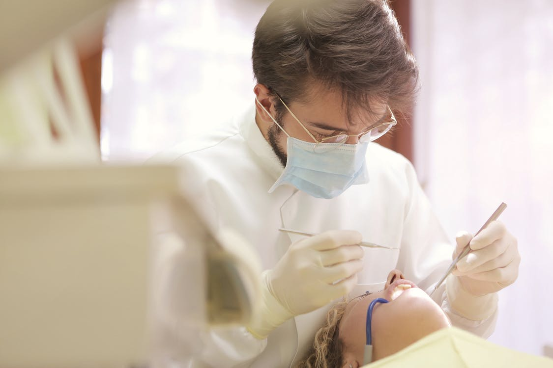 Man in white cleaning teeth