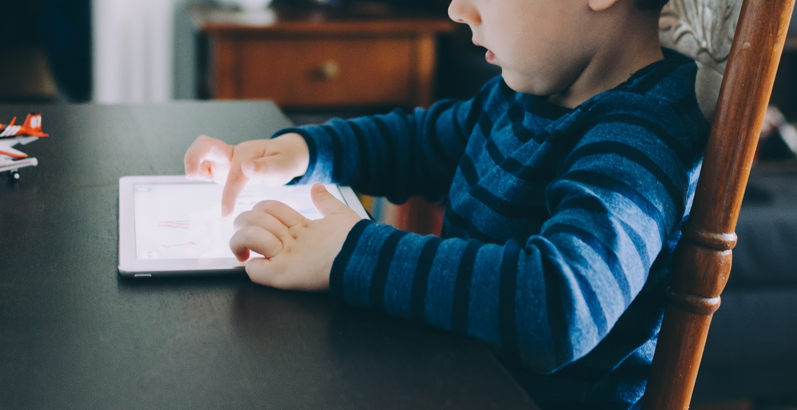 This is an image of a boy who is seated at a table using a tablet. This is what your child could look like after building a wifi robot at home with a robotics kit for kids.