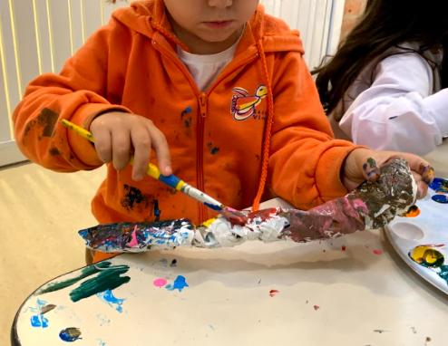A imagem mostra uma criança de moletom cor de laranja pintando uma lagarta produzida em papel.