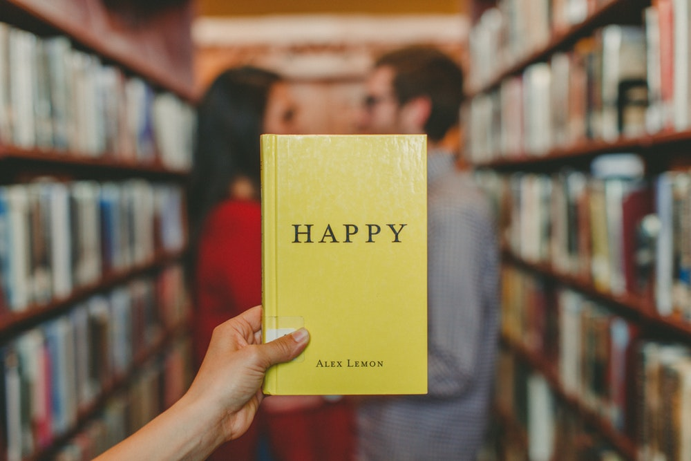 "Image of a book titled ""Happy"" super-imposed over a couple in a book shop"