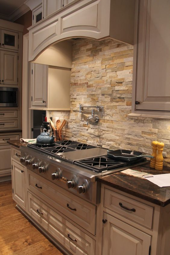 large traditional kitchen with off white cabinets, black hardware and warm colored stone backsplash