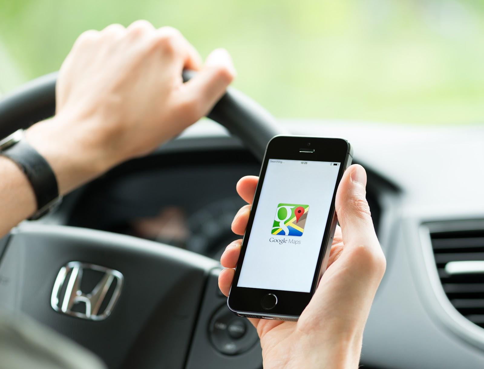 Homem dentro do carro olhando celular que está abrindo o google maps