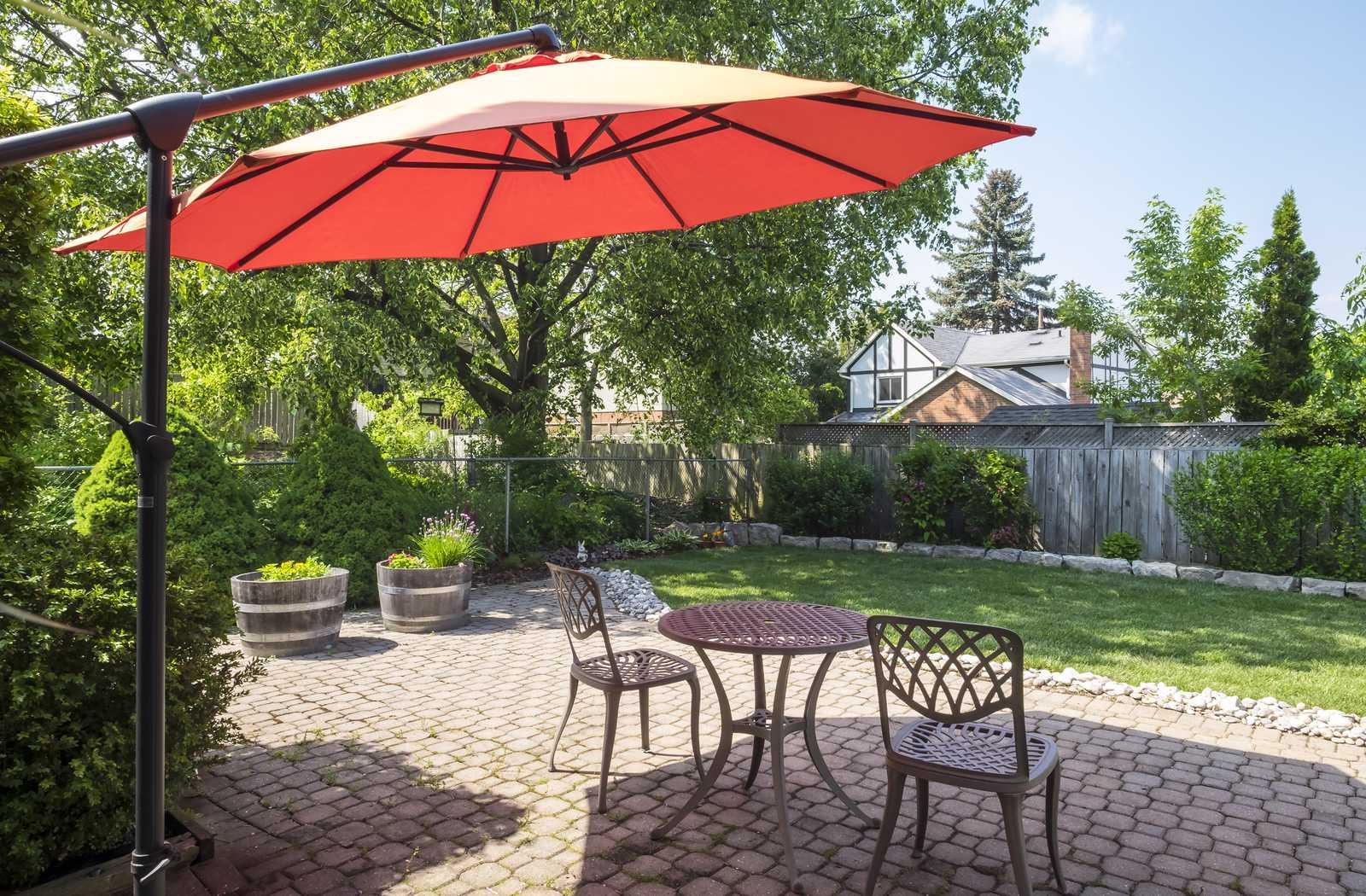 Cantilever orange umbrella shading bare patio furniture with greenery behind