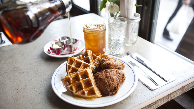Image of syrup being poured on to chicken and waffles
