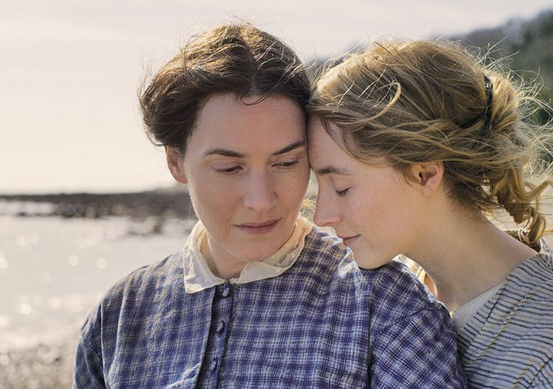 Kate Winslet and Saoirse Ronan in Ammonite (2020). The two women are standing on a beach in England, wearing dresses of the 1840s period in muted colours. Charlotte stands slightly behind Mary, resting her chin on Mary's shoulder tenderly.