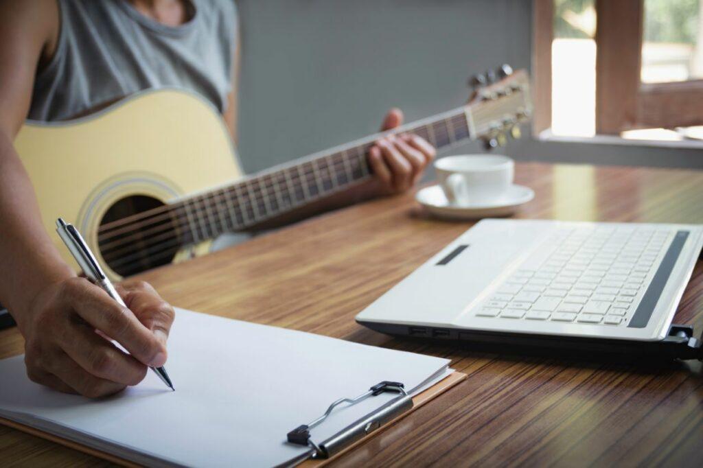 Un músico sosteniendo una guitarra acústica y anotando las notas musicales en la partitura